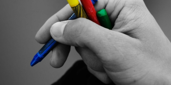Una mano scrive parole colorate