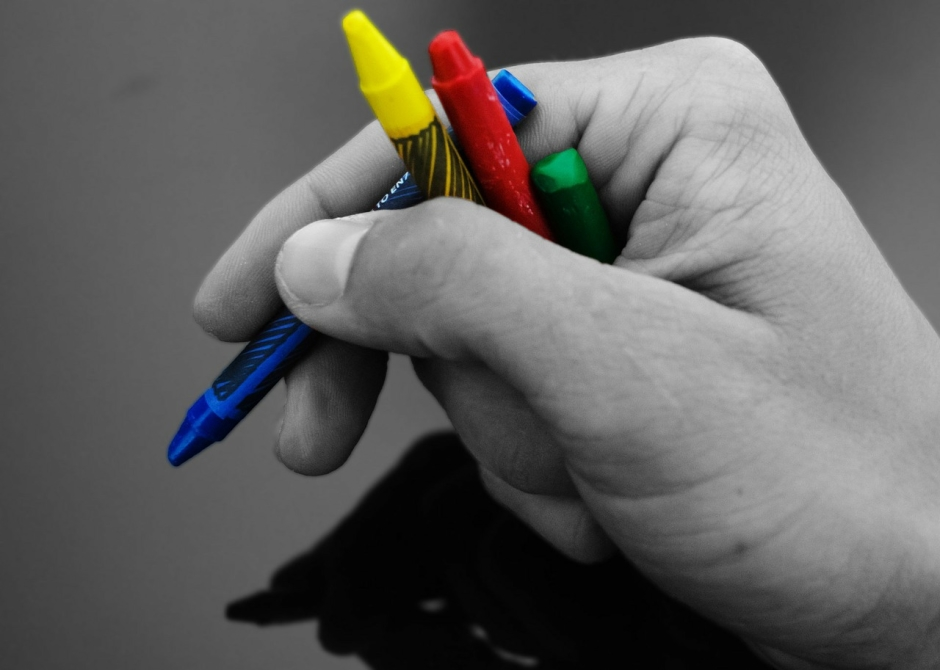 Una mano scrive parole colorate